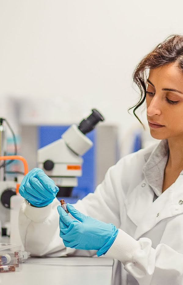 Woman in science lab wearing lab coat and medical gloves inspecting vial.