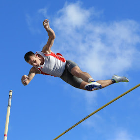 Clearing the bar.  by Ron Russell - Sports & Fitness Running ( grace, flying, sky, athletics., jumping, male, cloud, falling, pole vault, graceful, in flight, athlete, pole vaulter )