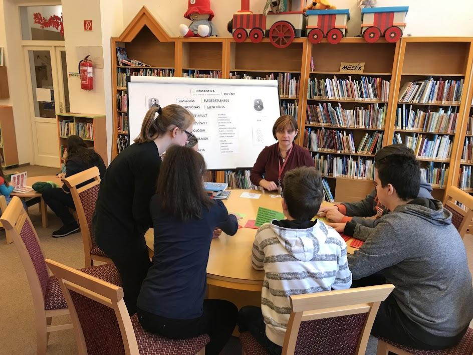 Asztalnál ülő diákok a könyvtárban