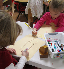 Children drawing a set-up of blocks.