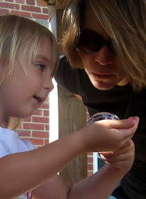 Child uses a magnifier and shows discovery to parent.