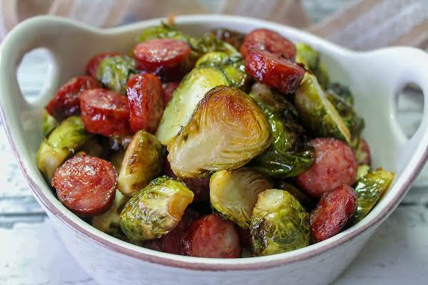 Crispy Brussels Sprouts With Andouille Sausage In A Bowl.