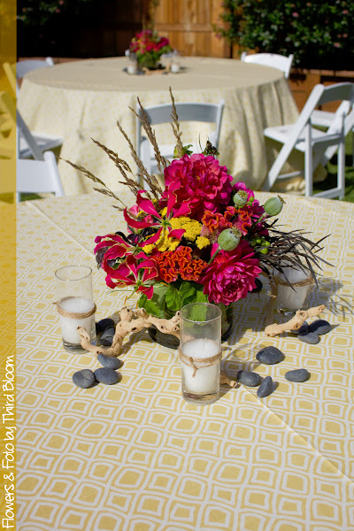Photo: The centerpieces sat atop retro yellow linens and had rocks, grape wood and votive candles with twine scattered around them.