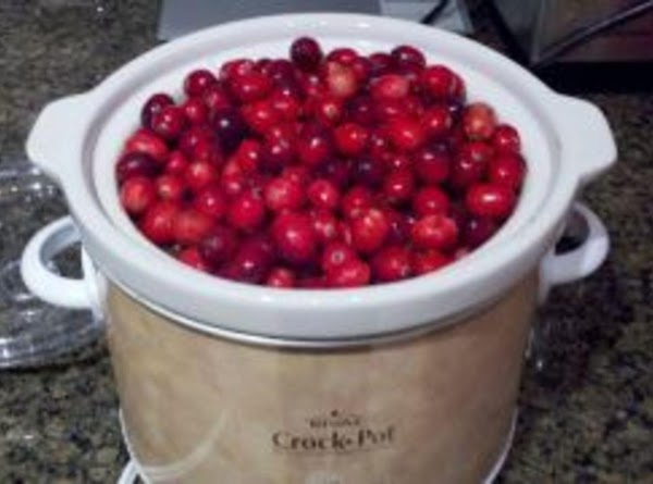 In a crock pot (at least 2.5qt size), add cranberries, sugar, spices, and pour...