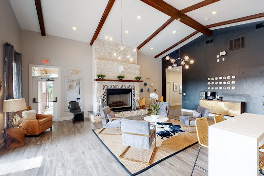 Community clubhouse with wood-inspired flooring, dark accent wall, stone fireplace, and seating