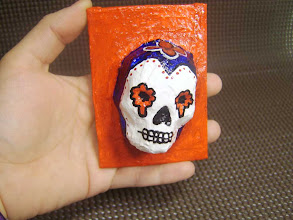 Photo: The Red White & Blue Sugar Skull. (sold) 2.5 x 3.5 x 1.5 inches. Acrylics on papier-mâché made from recycled store receipts. Sealed with a glossy varnish. Title and signature on the back. ©Marisol McKee.