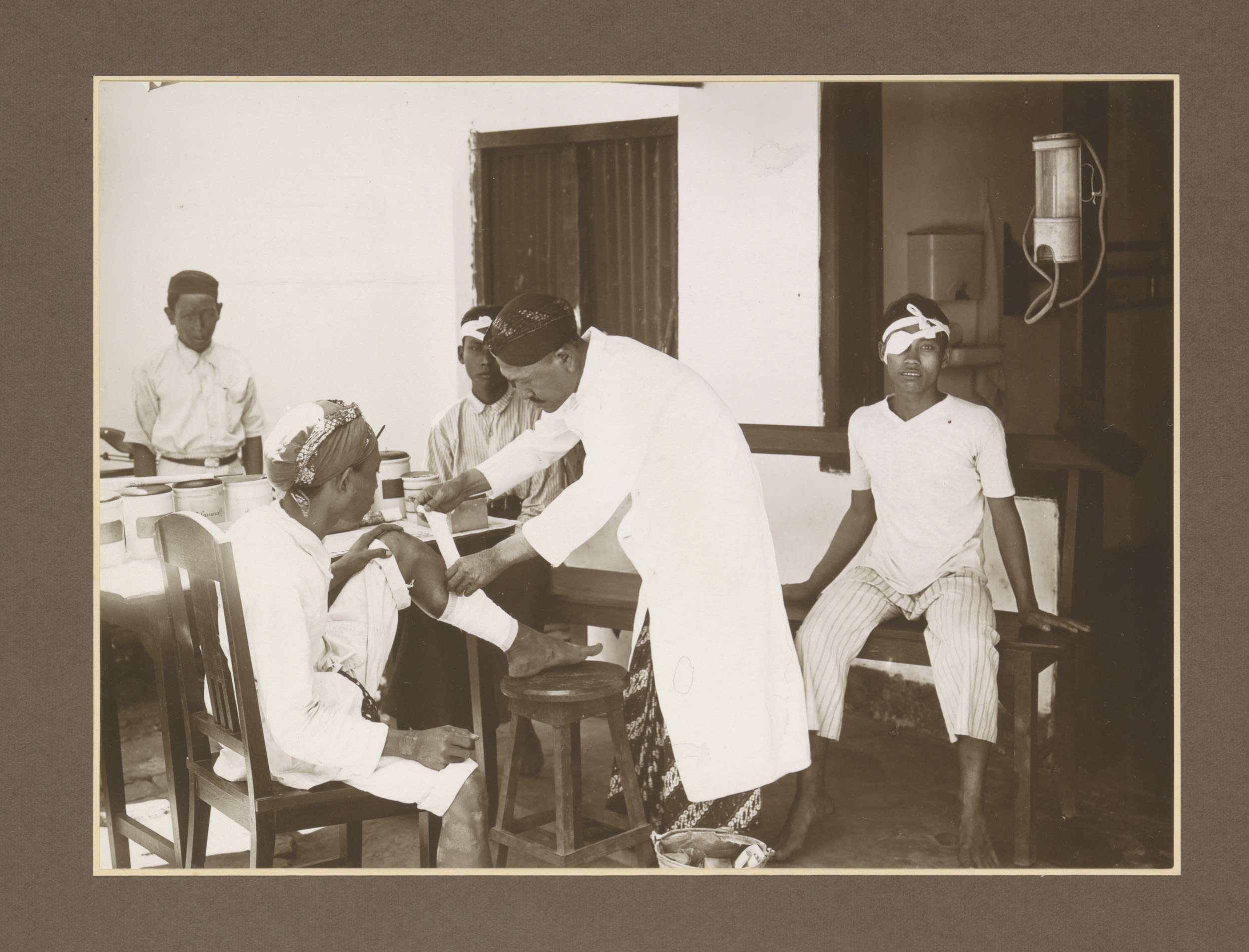 Mantriverpleger en patiënten in de polikliniek van suikerfabriek Boedoeran in Sidoarjo op Java