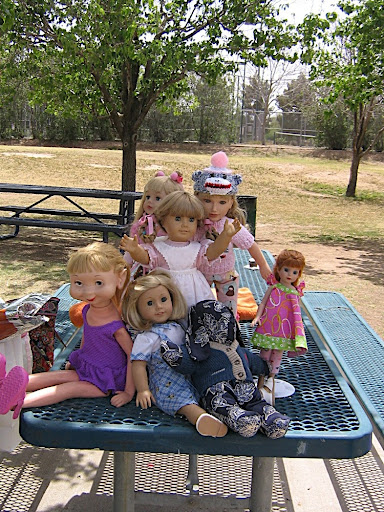 Kirsten sits among a Whimsy doll, a My Twinn, a stuffed bunny, and others.