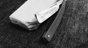 black and white image of straight blade on table