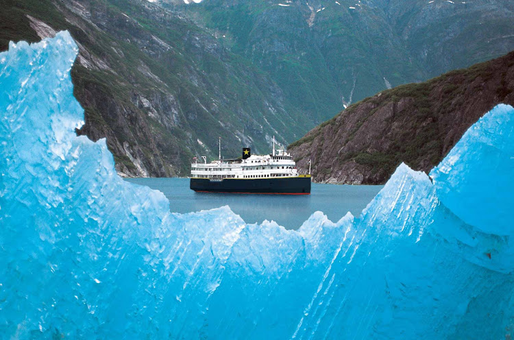 The S.S. Legacy, framed by blue ice, settles into a fjord in Alaska.