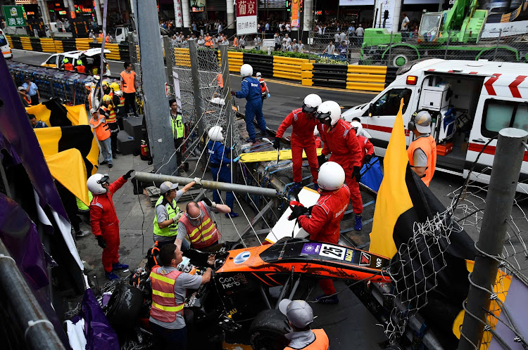 Race personnel and pit crew at the accident site after Sophia Floersch, a German driver of Van Amersfoort Racing flew over the barriers and crashed into a photographers' bunker at high speed during a Formula Three race at the Macau Grand Prix in Macau, China on Sunday.