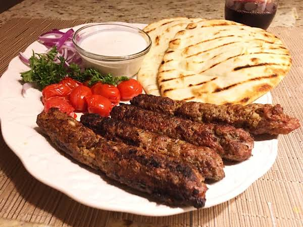 4 Kebabs On A White Plate Along With Naan Bread, Cherry Tomatoes, Sliced Red Onions, Parsley And A Sauce.