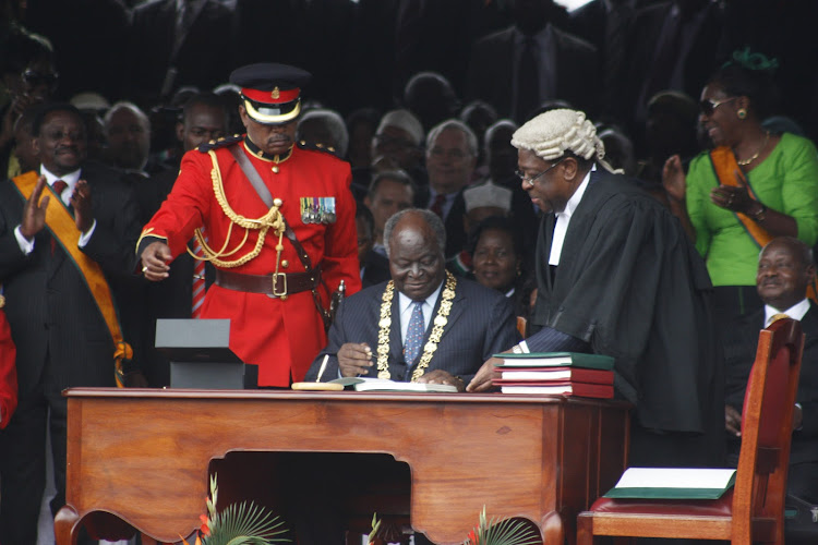 Former President Mwai Kibaki signs the documents of the new constitution as former AG Amos Wako looks on at Uhuru Park during the promulgation of the constitution ceremony in 2010.
