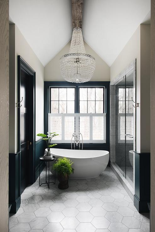 modern bathroom with freestanding tub, tile floors, large chandelier and potted plants