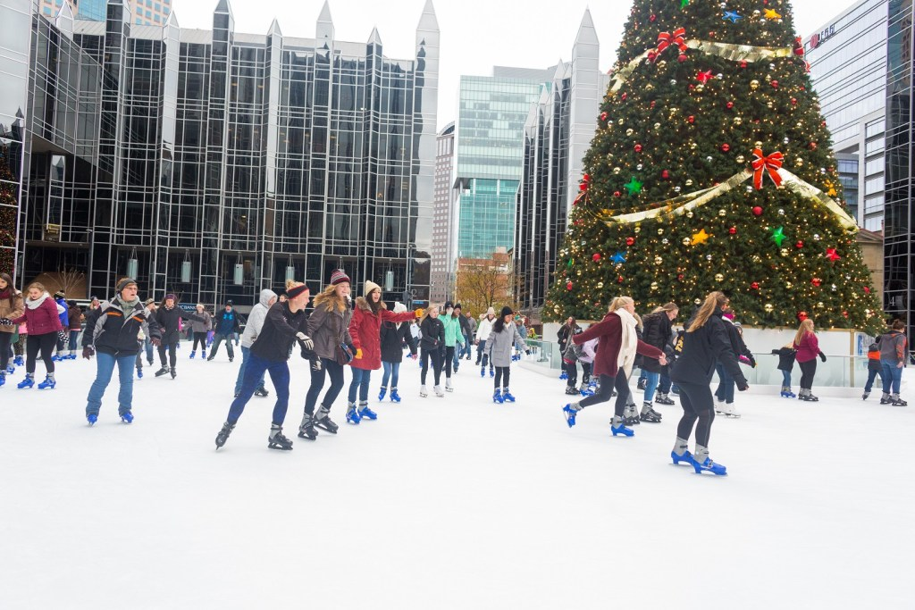 Skaters take to the ice on the rink at PPG place, a large Christmas treee and the iconic glass facade of the PPG Place building in the background.