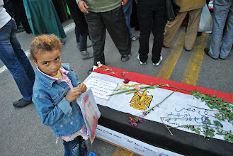 Photo: A young girl stands beside one of the symbolic caskets lining the Cabinet sit-in, each one representing an individual killed a week ago during the battle of Mohamad Mahmoud St.