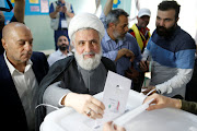 Lebanon's Hezbollah deputy leader Sheikh Naim Qassem casts his vote as he stands next to Hezbollah parliament candidate Amin Sherri at a polling station during the parliamentary election, in Beirut, Lebanon, May 6, 2018.