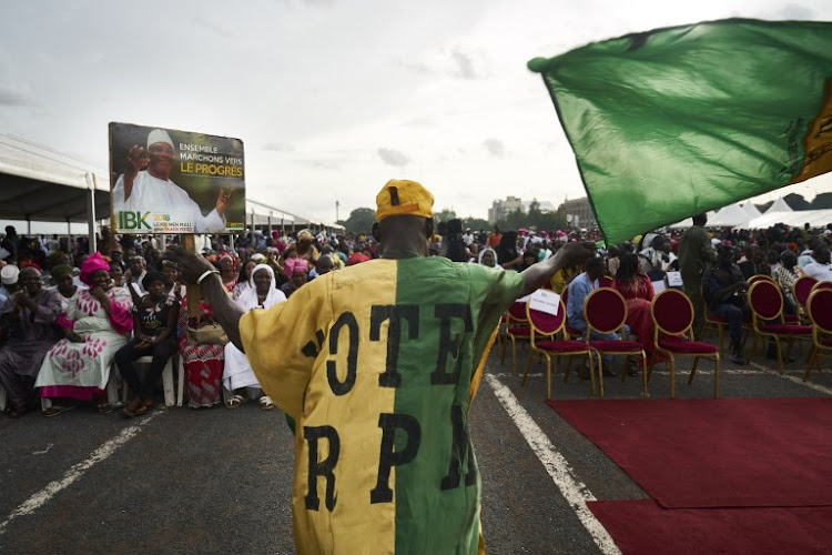 A supporter of Rally for Mali (RPM) political party waves a party flag during the last political rally of Mali's incumbent president Ibrahim Boubacar Keita, in Bamako on August 10, 2018, ahead of the runoff vote in Mali's presidential election on August 12.