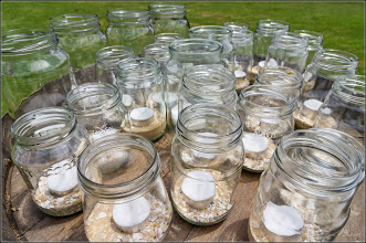 Photo: Candles in jars on a wine barrel
