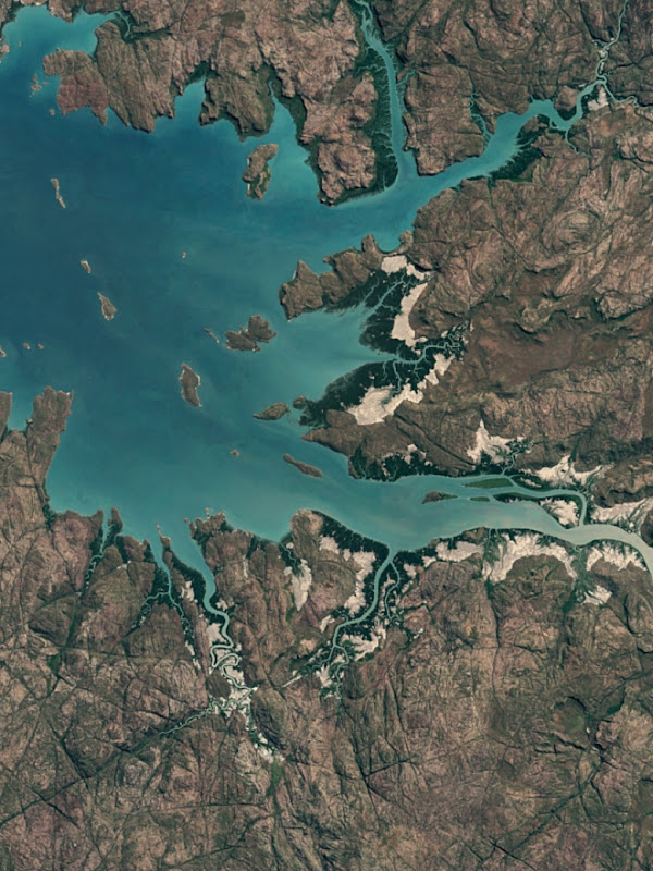 An aerial view of a body of water meeting the land.