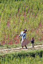 Photo: A woman and child walk through a rice field in Ambositra, Madagascar.