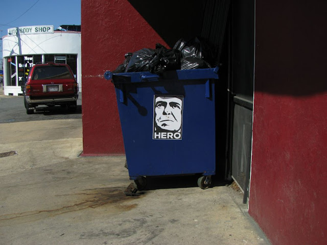 a dumpster with an interesting sticker on it