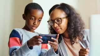 image of woman and young boy looking at phone
