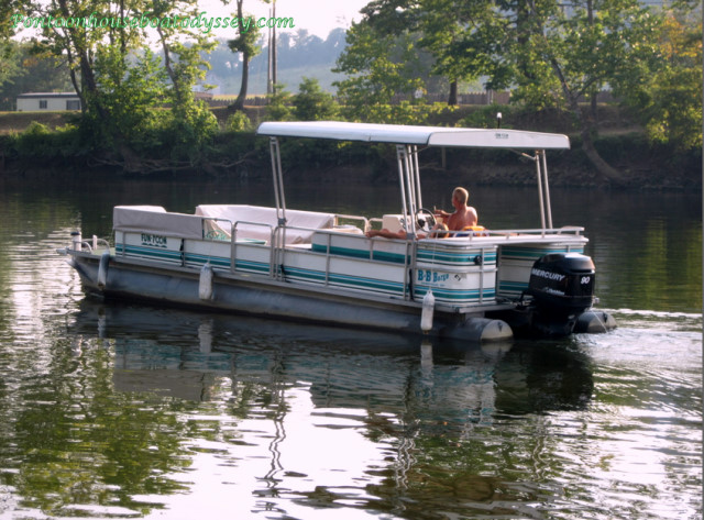A couple out for a relaxing cruise on their pontoon boat.