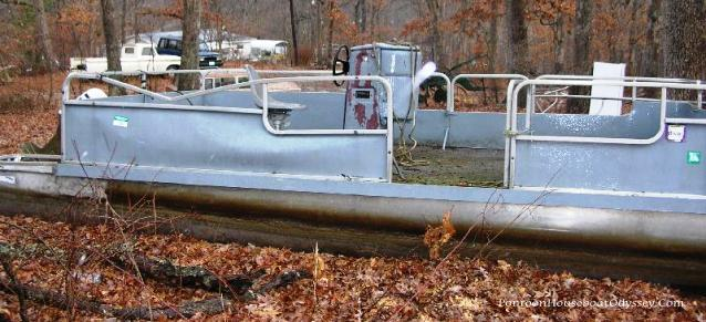 A deceptive looking pontoon boat that has been left sitting in a woodlot.