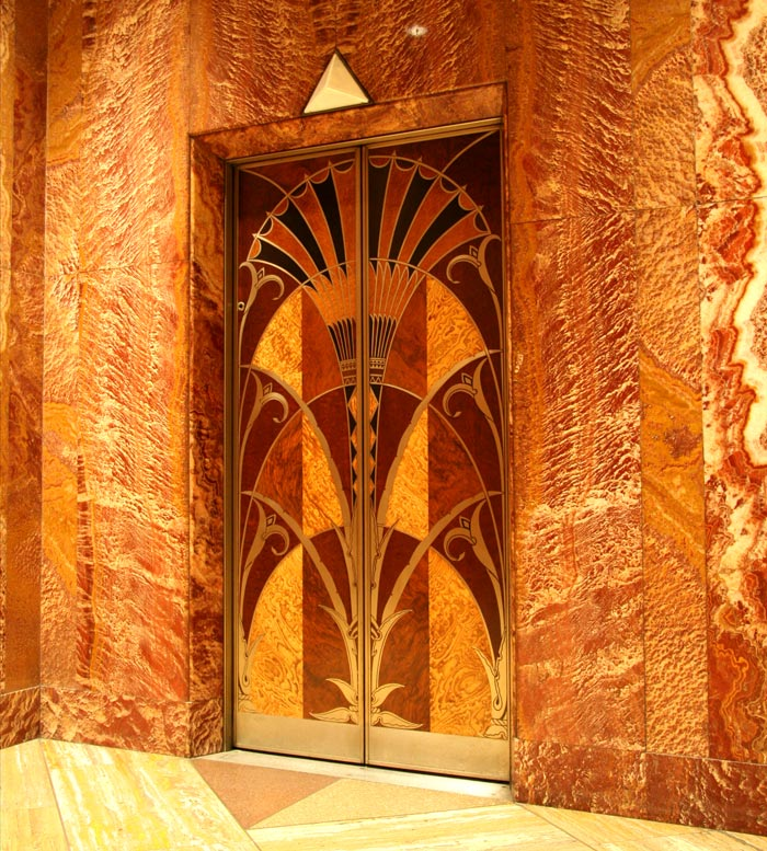 This is an elevator door from the Chrysler Building, set against red African