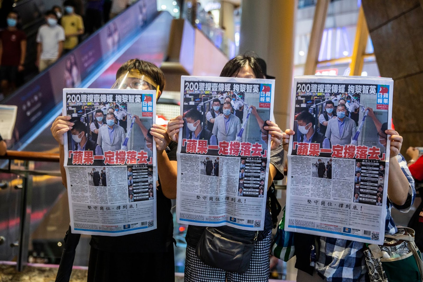 People hold up copies of Apple Daily as they protest for press freedom inside a mall in Hong Kong on August 11, 2020, a day after authorities conducted a search of the newspaper's headquarters following the arrest of founder Jimmy Lai under the new National Security Law. Hong Kongers rushed to buy pro-democracy newspaper Apple Daily on August 11 in a show of support for its owner, who was arrested a day earlier as police rounded up critics of China.