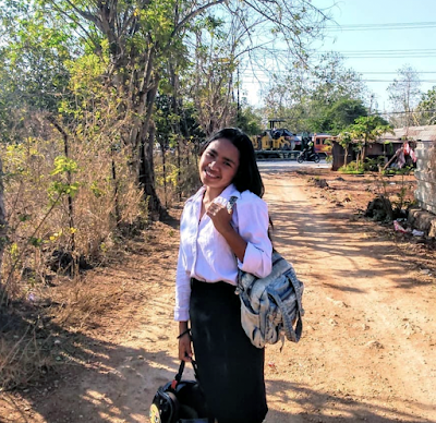 A photo of Sanchy smiling. She is a young woman wearing a backpack, standing outside on a sunny dirt road.