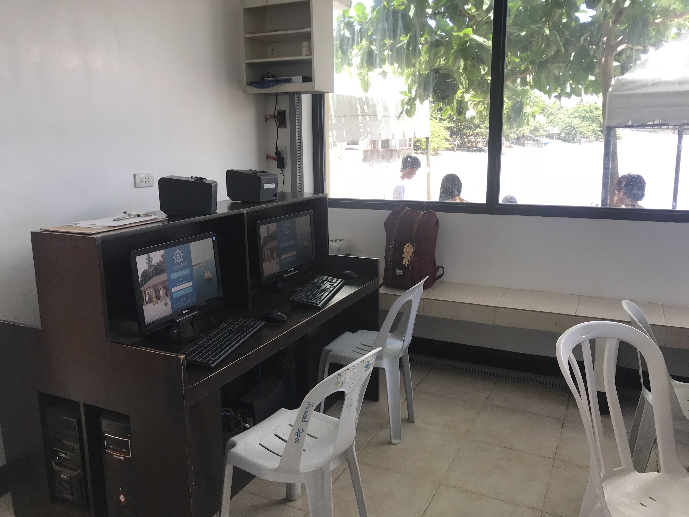 Two desktop on brown desk with two monobloc for Lakawon Island registration