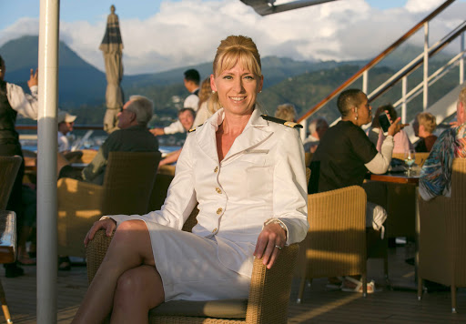 amanda-millar-aft-deck.jpg -  Amanda Millar, guest services director on Wind Surf, at sunset with St. Barts in the background.