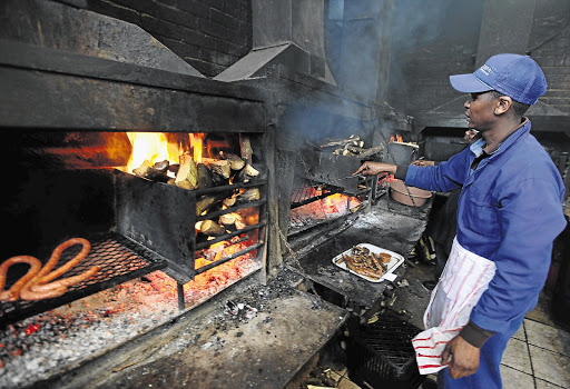 HOT STUFF: A staff member prepares meat for patrons at Mzoli's Place in Gugulethu, Cape Town.