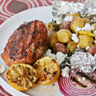 Grilled Greek-Style Meatloaf with Herbed Potatoes and Grilled Lemon.