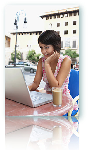 A woman sitting at a computer at a cafe.