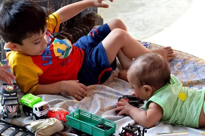 young brother playing with his baby brother