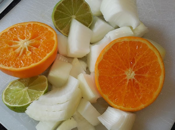 Cut the onion and garlic, juice the lime and cut the orange in half....