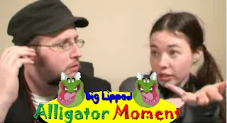 "Image: The Nostalgia Chick and the Nostalgia Critic cry ""BLAM"" behind an on-screen sign that reads ""big Lipped Alligator Moment,"" and depicts (you guessed it) a big-lipped alligator!"