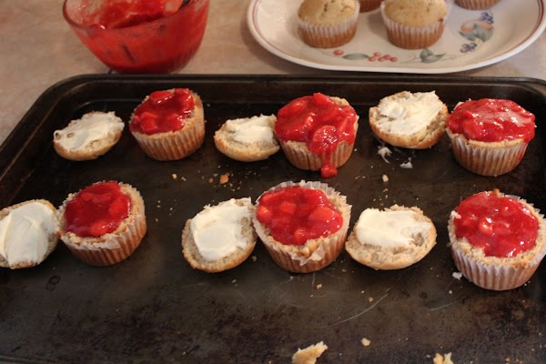 Spreading strawberry jam on top of cupcakes.