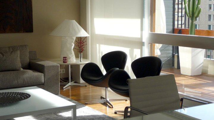 del diseo en el saln de esta vivienda de barcelona la aluminium chair de charlesuray eames y la butaca swan de arne jacobsen