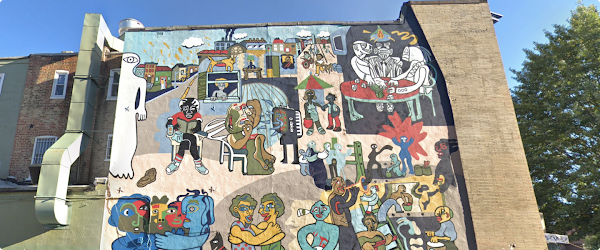 Mural painted on the side of a large building in Washington D.C. with many colors. Subjects in mural are playing games, having meals together, and hugging. Behind the building are large green trees and a blue sky.