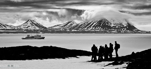 "Photo: Explorer's silhouette Svalbard, Norwegian Arctic From the photo of the day at http://www.kylefoto.com  Exploring the arctic tundra is somewhat of a contemplative activity. Mostly bare rocks will seem uneventful to the inattentive eye, but if you take your time you will become aware of the subtle flora that populates the land. As guides, we establish a perimeter where it's safe for us to explore, investigating the land for polar bears and keeping armed guides within view of everyone and everything just in case. This group was looking out into the horizon to our expedition vessel, the Akadamik Sergey Vavilov.  Photographic details: I noticed how at this moment everything seemed to just fit together. I often use the ""rule of thirds"" to line my subjects up and this is a great example. I split the image into thirds and my subjects are placed in the intersections of these divisions. The silhouette of the group and the ship are both important parts of the image but they are both 1 third of the way into the image. In addition the sky takes up the top third, the ocean the middle third and the land on the bottom third. The eye has a lot of paths to follow, from one subject to the other. The centre of the image has nothing in it, it forces the viewer to look around and linger a little longer on the photograph.  The original full colour photograph was interesting but I wanted more drama, it had a lot more details and I could even see the faces of the silhouettes. In lightroom I shifted to black and white and increased the blacks, this gave me the the contrasty look I wanted. check out the full post at http://www.kylefoto.com to see the original colour version.  1/400s f/8.0 ISO100 100mm"
