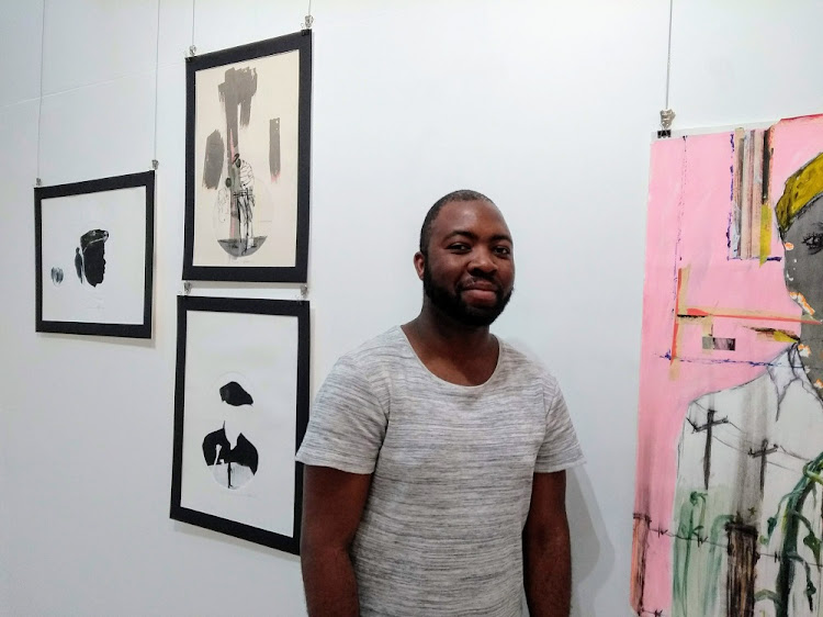 The artist poses for a photograph in front of one of his works. Picture: SUPPLIED