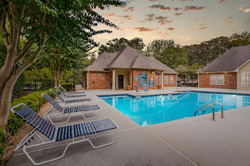 Refreshing swimming pool with lounge chairs by clubhouse at dusk