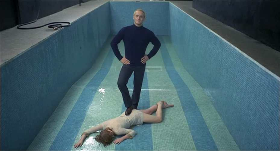 the picture is a POV from the camera's position that Sayer places after his punishment with water on Mary when he wants to take a victory photo by using the camera's timer. In the picture we see a more narrow but long empty swimming pool with small mosaic tiles in two colours - turquoise and a lighter blue-green - forming in total seven stripes of blocks of colour alternating beside each other on the bottom of the pool as the sides are only in turquoise. The hose Sayer used is seen on the poolside. Mary, wet and exhausted, is lying face down with her arms spread out and hair covering her face as Sayer stands proudly over her. Sayer stands with his hands on his hips, with a sly smile, and one foot on top of her body as a victory pose as he looks directly into the camera