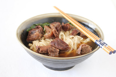 photo of a bowl of beef noodle soup with chopsticks resting on the rim
