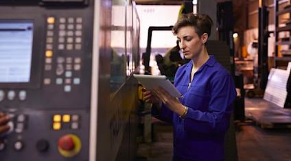Eine Entwicklerin prüft ein Tablet vor einer Maschine