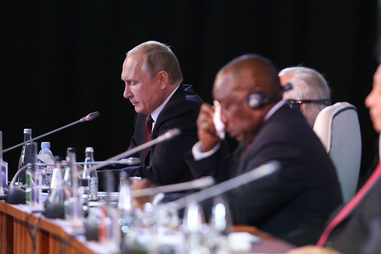 Russian President Vladimir Putin speaks as South African President Cyril Ramaphosa clears his face during the Outreach Dialogue session at the Brics Summit in Sandton, Johannesburg on July 27, 2018.